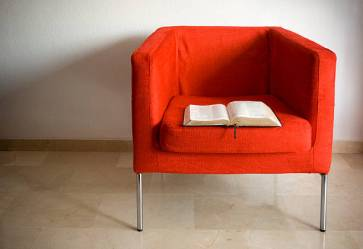 An open book sitting on a bright red modern chair.